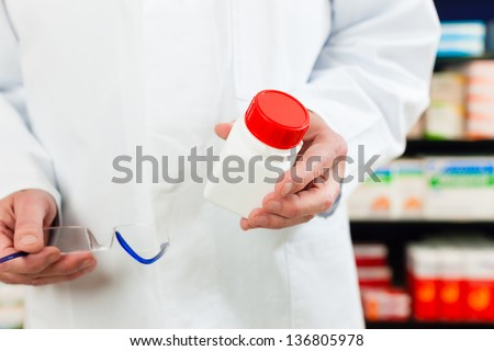 Pharmacist - only hands to be seen - standing in pharmacy with pharmaceuticals - stock photo