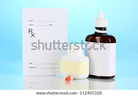 Pharmacist prescription with drops and pills isolated on blue - stock photo