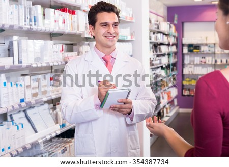 pharmacist serving  woman in pharmacy and smiling - stock photo