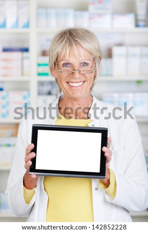 Pharmacist showing a tablet and smiling confidently - stock photo