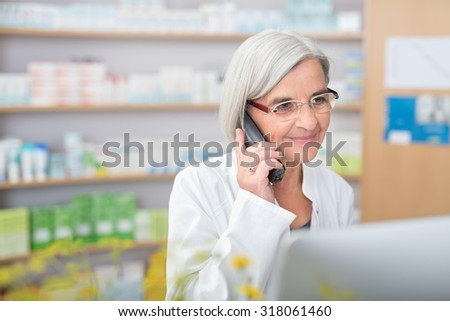 Pharmacist smiling as she takes a phone call listening to the patient on the line and checking information on her desktop computer as she tries to assist them - stock photo