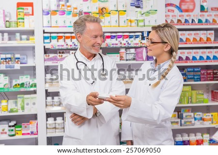 pharmacist speaking with his trainee about medicine in the pharmacy - Pharmacist Trainee