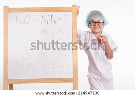 Pharmacist standing at the blackboard with a test tube - stock photo