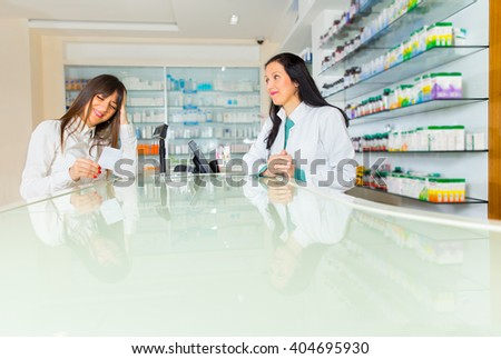 Pharmacist suggesting medical drug to buyer in pharmacy drugstore, selective focus - stock photo