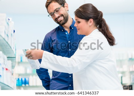 Pharmacist talking to customer in drug store, woman and man standing in front of shelves