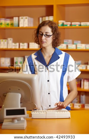 Pharmacist typing on computer behind pharmacy counter