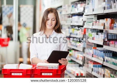 Pharmacist using a digital tablet while filling prescriptions - stock photo