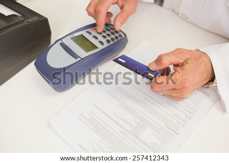 Pharmacist using keypad and holding credit card in the pharmacy