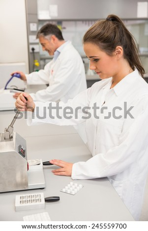 Pharmacist using press to make pills at the laboratory