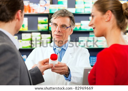 Pharmacist with customers in pharmacy, he is holding a bottle with pharmaceuticals in his hand - stock photo