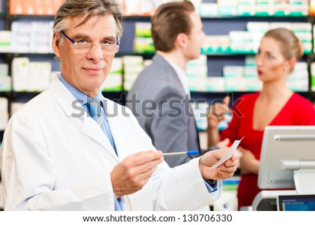Pharmacist with customers in pharmacy, he is holding a prescription slip in his hands - stock photo