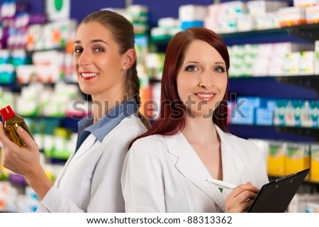 Pharmacist with female assistant in pharmacy standing in front of shelf with drugs