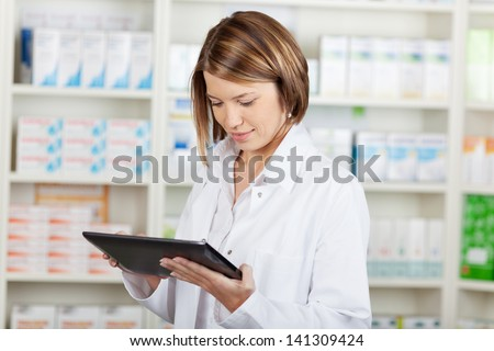 Pharmacist working with a tablet-pc in the pharmacy holding it in her hand while reading information - stock photo