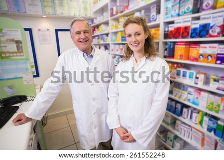 Pharmacists looking at the camera in the pharmacy - stock photo