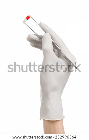 Pharmacology and Medical theme: doctor's hand in a white glove holding tweezers with red pill capsule isolated on white background in studio - stock photo