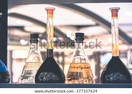 Pharmacy and chemistry theme. Test glass flask with solution in research laboratory. Shallow DOF. fade filter - stock photo