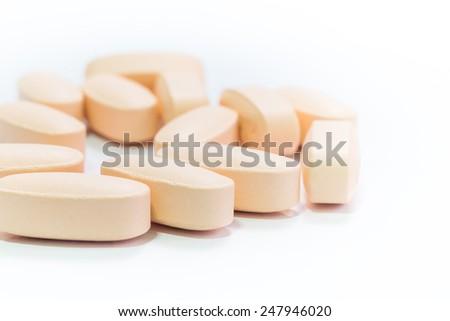 Pharmacy theme, Heap of orange round medicine tablet pills. Shallow depth of field - stock photo