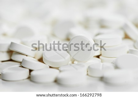 Pharmacy theme, Heap of white round medicine tablet antibiotic pills. Very Shallow DOF - stock photo