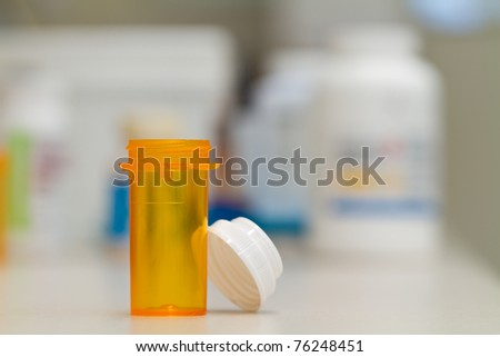 pharmacy vial, empty, in a pharmacy, stock bottles in the background