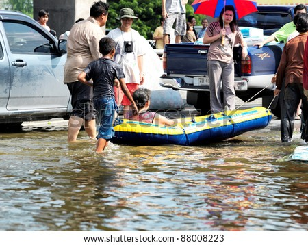 PHATHUMTRANI, THAILAND- OCTOBER 21: Volunteers rescue elderly woman during  worst flooding in decades on October 21, 2011 Rongsit Road, Phathumtrani, Thailand.