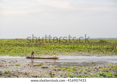 PHATTHALUNG, THAILAND- April 23: Fishermen are rowing their boat in Thale Noi Waterfowl Reserve on April 23, 2016 in Phatthalung, Thailand.