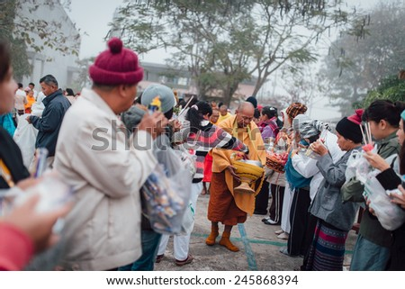 PHAYAO , THAILAND - DECEMBER 29: People Give food offerings to a Buddhist monk on December 29, 2014  in Phayao, Thailand. Thai traditional, people will make merit making by give food to monk  - stock photo