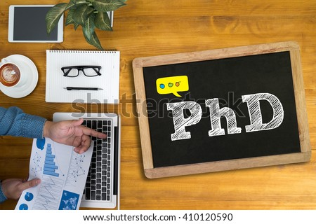 PhD Doctor of Philosophy Degree Education Graduation Businessman working at office desk and using computer and objects, coffee, top view, - stock photo