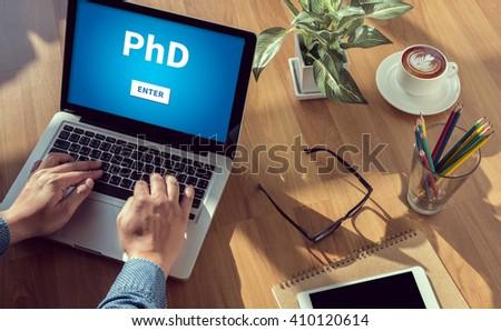 PhD Doctor of Philosophy Degree Education Graduation man hand on table Business, coffee, Split tone - stock photo