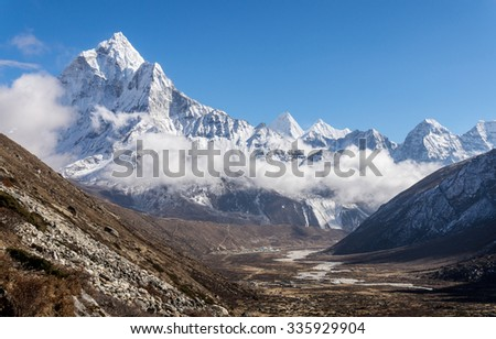 Pheriche valley on the way to Everest Base Camp with snowy mountains in the background. Mount Ama Dablam is on the left. - stock photo
