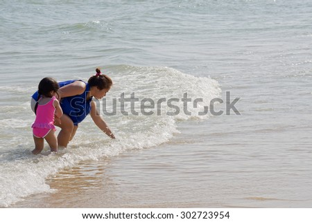 PHETCHABURI, THAILAND - JANUARY 3: Unidentified tourists resting on the beach at Cha - am on January 3, 2015 in Petchaburi, Thailand. Cha - am beach is the famous seaside resort in Thailand.  - stock photo