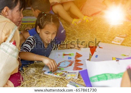 Phichit / Thailand - January 09 2016: [Thai girl drawing a picture to give to her father and mother in Children's Day at Phichit, Thailand ].