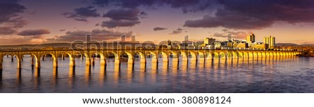 Philadelphia and Reading Railroad Bridge crosses Susquehanna river at sunset. Harrisburg skyline shines under a late afternoon light. - stock photo