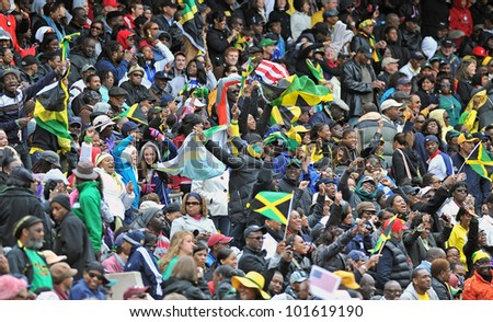 PHILADELPHIA - APRIL 28: Fans, many waving Jamaican flags, stand and cheer during a USA vs the World heat at the Penn Relays April 28, 2012 in Philadelphia. - stock photo