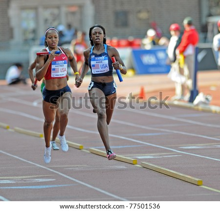 PHILADELPHIA - APRIL 30: Natasha Hastings (l) & Keshia Baker (r), head into the shade on the back straight during the Olympic Development 4x400 ladies relay at the 117th Penn Relays in Philadelphia. - stock photo