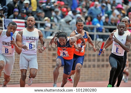 PHILADELPHIA - APRIL 28: The Syracuse 4x100 men's relay team (A) makes the final baton exchange during the ECAC championships at the 2012 Penn Relays April 28, 2012 in Philadelphia. - stock photo