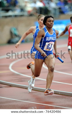 PHILADELPHIA - APRIL 28: Two Members of the University of Buffalo's women's 4x100 relay team complete the final baton hand-off in a heat at the 117th Penn Relays on April 28, 2011 in Philadelphia, PA