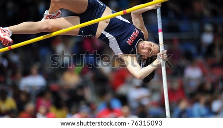 PHILADELPHIA - APRIL 28: Unidentified Penn female pole vaulter goes up and over the bar during the ladies college competition at the 177th Penn Relays on April 28, 2011 in Philadelphia, PA