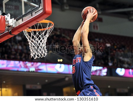 PHILADELPHIA - FEBRUARY 28: Detroit Titans guard Ray McCallum (3)flies in to slam the ball for a dunk during the basketball game February 28, 2013 in Philadelphia. - stock photo