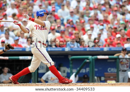 PHILADELPHIA - JULY 26: Philadelphia Phillies catcher Paul Bako swings and misses at a pitch, with eyes closed, during the July 26, 2009 game in Philadelphia. - stock photo