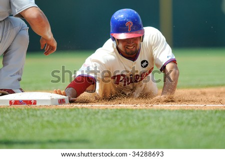 PHILADELPHIA - JULY 26: Philadelphia Phillies center fielder dives back safely to first base on a pick off attempt during the July 26, 2009 game in Philadelphia. - stock photo