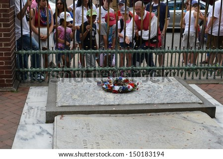 PHILADELPHIA- JULY  4: Tourists gather to toss coins on Benjamin Franklin's grave during Independence Day Celebrations on July 4, 2013 in Philadelphia, PA. - stock photo