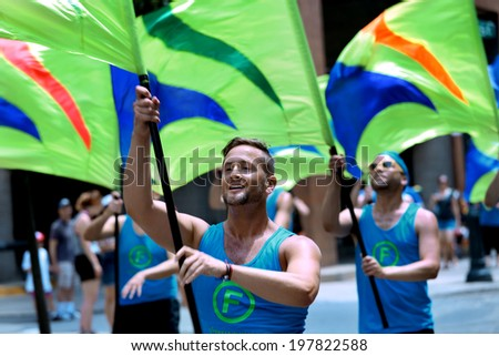PHILADELPHIA - JUNE 8: Flaggots colorguards spinning flags at the 26th Annual Pride Parade on the streets of Center City Philadelphia on June 8th, 2014 in Philadelphia.   - stock photo