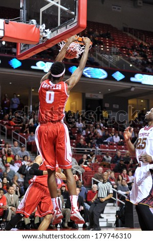 PHILADELPHIA - MARCH 1: Houston forward Danrad Knowles (0) scores on a slam dunk during the AAC basketball game March 1, 2014 in Philadelphia.  - stock photo
