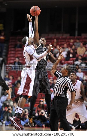 PHILADELPHIA - MARCH 4: UCF Knights forward Staphon Blair (52) jumps against Anthony Lee (3) for the start of overtime in the AAC college basketball game March 4, 2014 in Philadelphia.  - stock photo