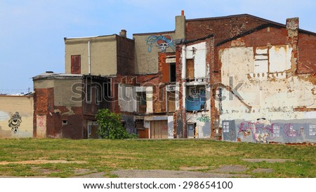 PHILADELPHIA - MAY 18: Walking by an old, abandoned building left in disrepair on May 18, 2015 in Philadelphia. - stock photo