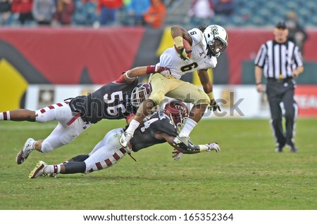PHILADELPHIA - NOVEMBER 16: Temple linebacker Sharif Finch (56) lays out to try to tackle a UCF receiver during the AAC college football game November 16, 2013 in Philadelphia. - stock photo