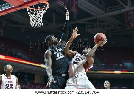 PHILADELPHIA - NOVEMBER 30: Temple Owls guard Will Cummings (2) tries to get up a contested shot over a LIU defender during the NCAA basketball game November 30, 2014 in Philadelphia. - stock photo