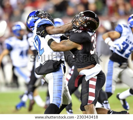 PHILADELPHIA - NOVEMBER 8: Temple Owls linebacker Nate D. Smith (35) blocks a Tiger defender on special teams during the AAC football game November 8, 2014 in Philadelphia, PA.  - stock photo