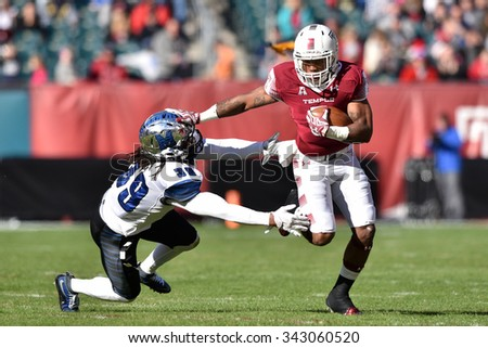 PHILADELPHIA - NOVEMBER 21: Temple Owls running back Jahad Thomas (5) stiff arms a defender during the AAC football game November 21, 2015 in Philadelphia.  - stock photo