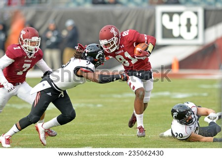 PHILADELPHIA - NOVEMBER 29: Temple Owls wide receiver Brodrick Yancy (81) tries to break a tackle after a catch during the football game November 29, 2014 in Philadelphia. - stock photo